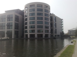 Round tower of office building beside corner of canal