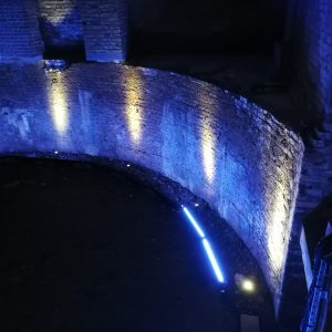 A curved wall is lit by blue wall-wash and white spotlights in a cavern-like setting